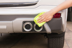 Hand with yellow microfiber cloth cleaning big white taillight c Royalty Free Stock Image