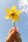 Hand with yellow pinwheel. On clear blue sky Stock Images