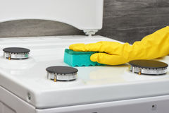 Hand in yellow rubber cleaning white stove with green sponge Stock Photo
