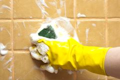 Hand in yellow rubber glove Stock Image