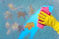 Hand in yellow rubber glove cleaning window Stock Images