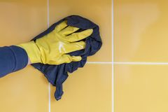 hand in a yellow rubber glove washes a yellow wall with a rag stock images
