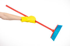 Hand in yellow rubber gloves holding a red broom  Stock Photo
