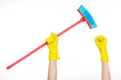 Hand in yellow rubber gloves holding a red broom  Royalty Free Stock Image
