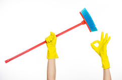 Hand in yellow rubber gloves holding a red broom. Cleaning the house topic: human hand in yellow rubber gloves holding a red broom  on a white background Stock Images