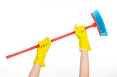 Hand in yellow rubber gloves holding a red broom. Cleaning the house topic: human hand in yellow rubber gloves holding a red broom  on a white background Stock Photo