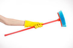 Hand in yellow rubber gloves holding a red broom  Royalty Free Stock Images