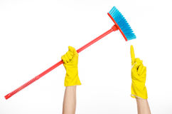 Hand in yellow rubber gloves holding a red broom  Royalty Free Stock Photos