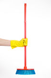 Hand in yellow rubber gloves holding a red broom  Stock Image