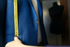 Tailor`s hands making measurements of a suit. Hand with yellow tailor`s ruler. Close up of man in blue suit Stock Photo