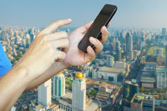 Hand of Young adult Tourist use Mobile Device smartphone over Ci Royalty Free Stock Image