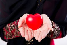 Hand of young asian muslim woman holding red heart shaped pillow closeup Royalty Free Stock Photography