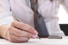 Hand of the young busines-lady. Holding the pen in it Stock Image