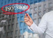 Hand of young businessman write the word ISO 18000 on skyscraper Royalty Free Stock Photo