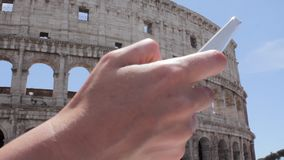 Hand young caucasian woman tourist texting on beautiful view of european ancient city with mobile smart phone