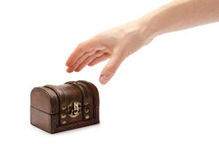 Hand of young girl holding glass of rum with coke. Female hand holding treasure chest. Isolated on white background Royalty Free Stock Photo