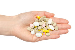 Hand of young girl holding pills. Royalty Free Stock Image