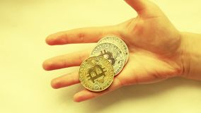 The hand of a young girl holds a bitcoin coin close-up in a slow motion. Crypto currency in the hands of the girl. Slow motion stock video