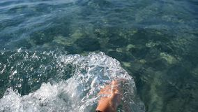 The splashes in the sea. The hand of a young girl joyfully splashes in the sea water stock video