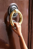 Hand of young girl knocks on the door with the big brass handle Stock Images