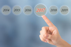 Hand of a young girl points to a figures 2017 opposite beautiful Stock Photos