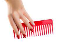 The hand of a young girl takes the red plastic brush Royalty Free Stock Images