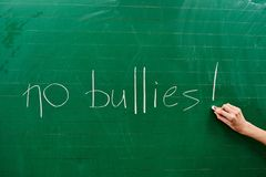 Hand of a young girl writing the words NO BULLIES on the green school board royalty free stock photos