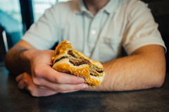 Hand of a young man holding a burger. Hands of a young man in a white shirt holding holding fast food Royalty Free Stock Photos