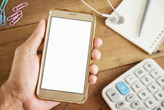 Hand of young man holding smart phone mobile. White screen with notepad and calculator on office table vintage style Royalty Free Stock Photos