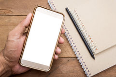 Hand of young man holding smart phone mobile. White screen with notepad and pencil on vintage table Royalty Free Stock Images