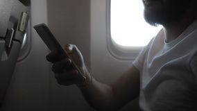 Hand of young man holding smartphone in the plane, close up. Male passenger with beard, in white t-shirt, is scrolling down the screen of his brand-new device stock video footage