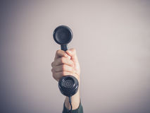 Hand of young man holding vintage phone Royalty Free Stock Images