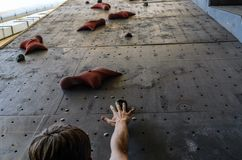 Hand of the young man on a hook of the artificial climbing wall royalty free stock photo