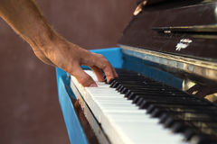 A hand of a young man playing piano on a street of city. A hand of a young man playing piano on a street of city, closeup Stock Image