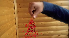 From the hand of a young man pouring a bunch of hearts stock footage