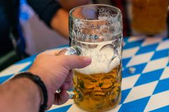 Hand of young people lifting glasses of beer at the Oktoberfest germany Soft focus. Shallow DOF royalty free stock photo