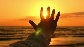 The hand of a young woman close-up, touching the sunlight, against the background of the sea sunset in slow motion. Happy girl looking at the shining sun of stock footage