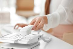 Hand of young woman picking up telephone receiver. For making call in office Stock Photos