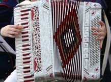 Hand of a young woman plays the ancient accordion Stock Photos