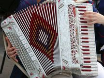 Hand of a young woman plays the ancient accordion Royalty Free Stock Image