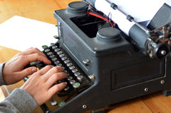 Hand of a young woman writer writing on antique typewriter Stock Photography