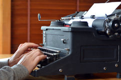 Hand of a young woman writer writing on antique typewriter Stock Photo