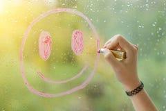 Hand zeichnet einen positiven smiley auf einem regnerischen Herbstfenster Lizenzfreies Stockfoto