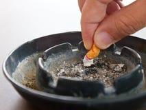 Hand zerquetscht Zigarette im Aschenbecher und im Rauche auf dem Tisch lizenzfreie stockfotografie