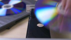 Hand zieht die Diskette vom Kasten und vom Einsatz zum DVD-Spieler stock footage