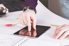 Hand zooming in. Male hand zooming in on tablet placed on large whatman with office tools Stock Photo
