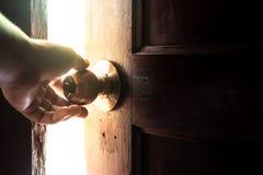 Hand, zum der Tür zum Licht zu öffnen Stockfotografie