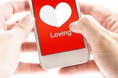 Hand zwei, die an Smartphone mit Herzform und liebevollem Wort hält Lizenzfreies Stockbild