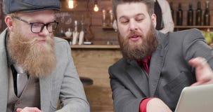 Handabschluß herauf Schuss des jungen Geschäftsmannes zwei, der über einem Unternehmensplan debattiert stock video
