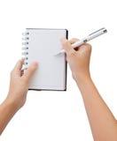 handanteckningsbokpennan skriver Arkivbild